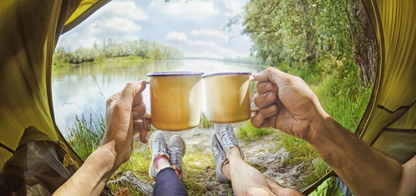 Young couple sitting   in the tent and drinking tea while looking on the Desna river , Ukraine