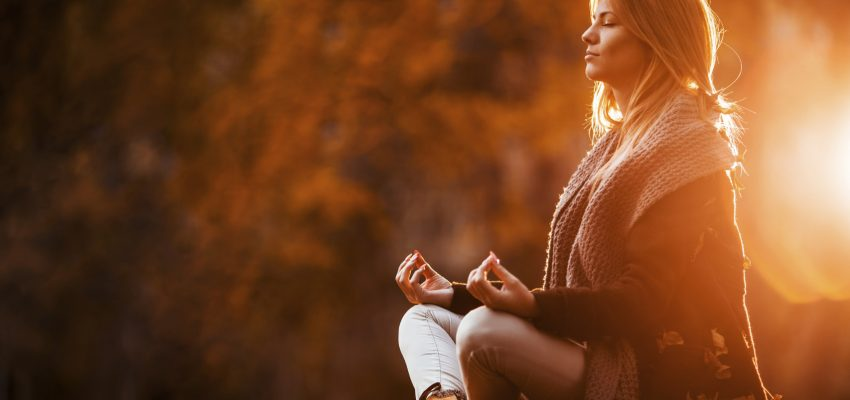 Young woman sitting in Lotus position at the park and doing breathing exercises.