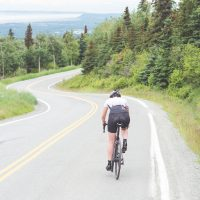 Female cyclist cruises along a rural highway on a dry and moderate morning. Ahead of her is a bend, and beyond that is a valley. Rear view shot.
