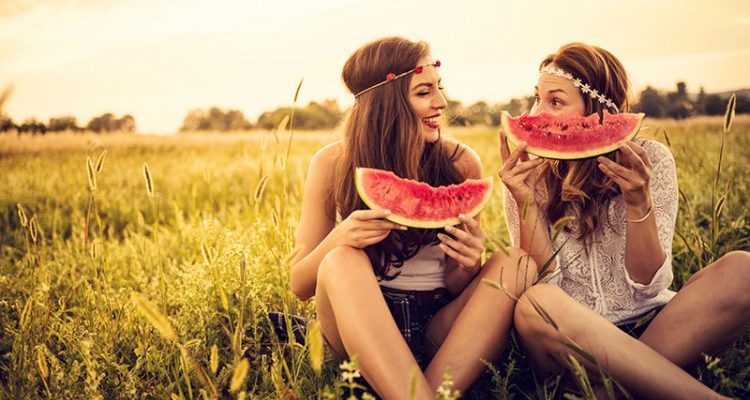 Two ladies eating watermelon