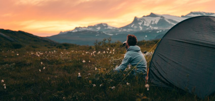 Tent on a mountain top during sunset, man looking on view. Rago National Park, Norway